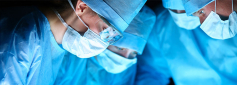 4 surgeons looking down and wearing blue coats and sterility masks